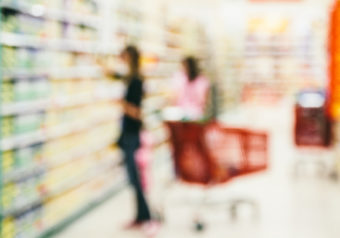 People on a supermarket with shopping carts - blurred image